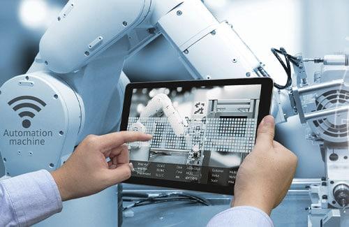 Hand tippt auf Screen und steuert automatisierten Roboter