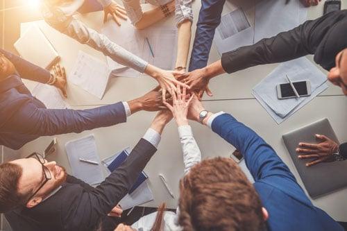 Team mit Händen in der Mitte zur Darstellung von Devops als Mindset