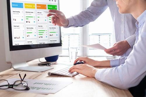 Hände zeigen auf einen Bildschirm, der komplexe Daten darstellt.