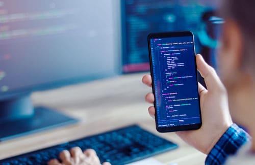 Handy mit Software-Code zur Darstellung von App Entwicklung