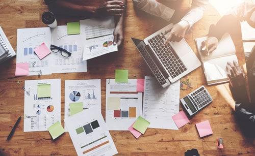 Tisch mit Papieren und Notebook zeigt agile Projekt Planung
