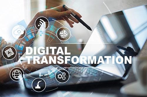 Hand zeigt auf Notebook darüber steht Digital Transformation.