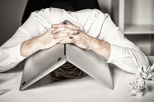 Mann hat Kopf auf dem Tisch und Notebook über sich