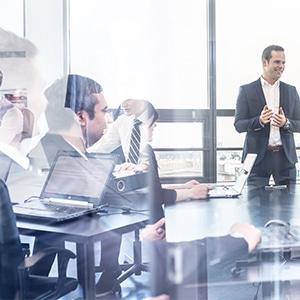 Mitarbeiter erklärt drei weiteren Mitarbeitern etwas im Interim Management Training.