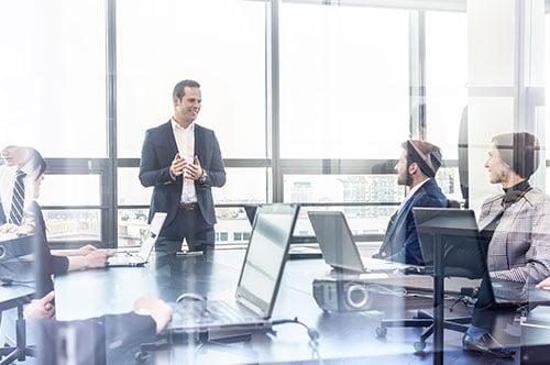 Mitarbeiter erklärt drei weiteren Mitarbeitern etwas im Management Training.